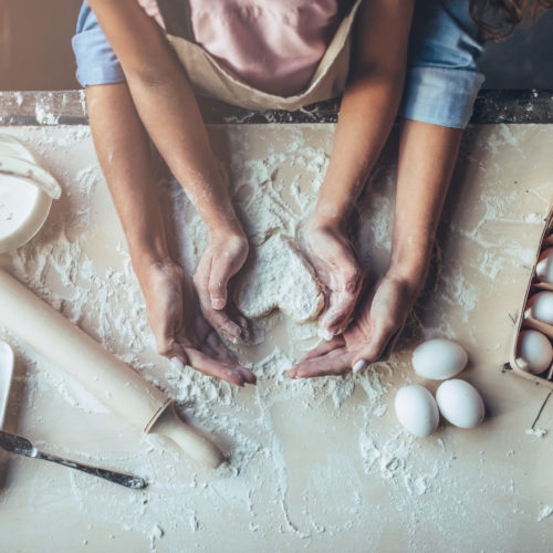 Top view of mom with daughter making dough heart surrounded by baking utensils.